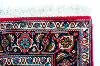 The edge of a Persian rug is shown in close up.